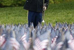 Sgt. Samuel Costa, of Somerset, Mass., salutes after playing taps at the Massachusetts Military Heroes Fund flag garden on Boston Common in Boston, ahead of Memorial Day, Thursday, May 21 2015. Each of the approximately 37,000 flags represents a Massachusetts military member who died in service from the Revolutionary War to the present. (AP Photo/Michael Dwyer)