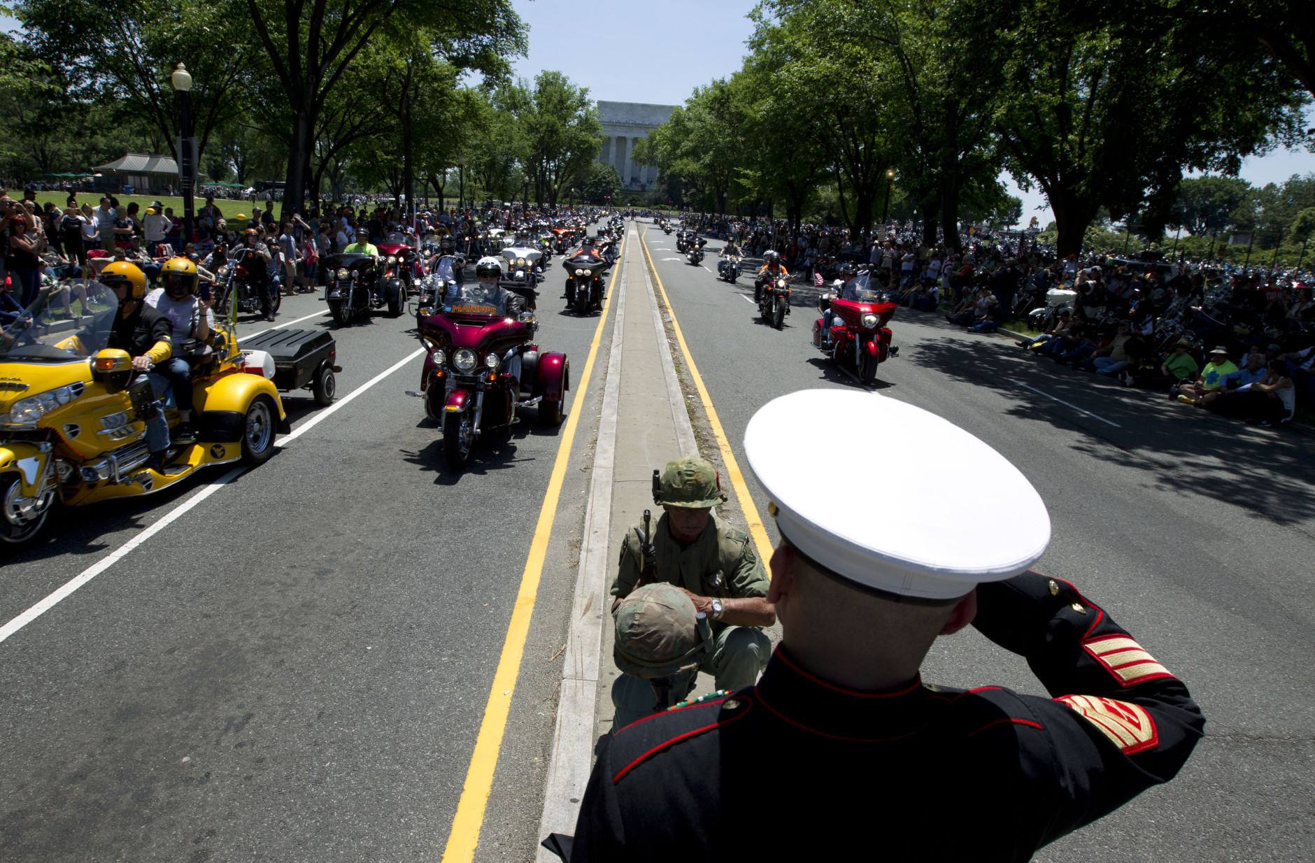 CORRECTS SPELLING TO TIM NOT TIME   Marine Tim Chamber and Army Eric Cantu salutes as motorcycles drive past during the annual Rolling Thunder parade ahead of Memorial Day in Washington, Sunday, May 24, 2015. (AP Photo/Jose Luis Magana)