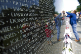 Visitors look at the names on the Vietnam Veterans Memorial wall, ahead of Memorial Day in Washington, Sunday, May 24, 2015.  (AP Photo/Jose Luis Magana)