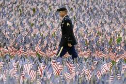 A soldier walks on a path through the Massachusetts Military Heroes Fund flag garden on Boston Common in Boston, ahead of Memorial Day, Thursday, May 21 2015. Each of the approximately 37,000 flags represents a Massachusetts military member who died in service from the Revolutionary War to the present. (AP Photo/Michael Dwyer)