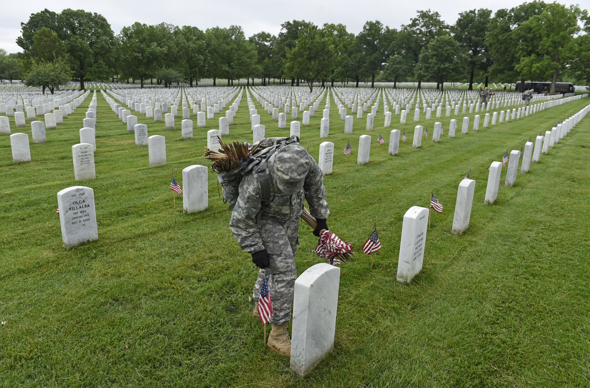 """Third U.S. Infantry Regiment (The Old Guard) Pfc. Kaitlyn Bolde of Scotia, N.Y., places a flag in front of a headstone at Arlington National Cemetery in Arlington, Va., Thursday, May 21, 2015.""""Flags In"""" is an annual tradition that is reserved for The Old Guard since its designation as the Army's official ceremonial unit in 1948. They conduct the mission annually at Arlington National Cemetery and the U.S. Soldiers' and Airmen's Home National Cemetery prior to Memorial Day to honor the nation's fallen military heroes. (AP Photo/Susan Walsh)"""