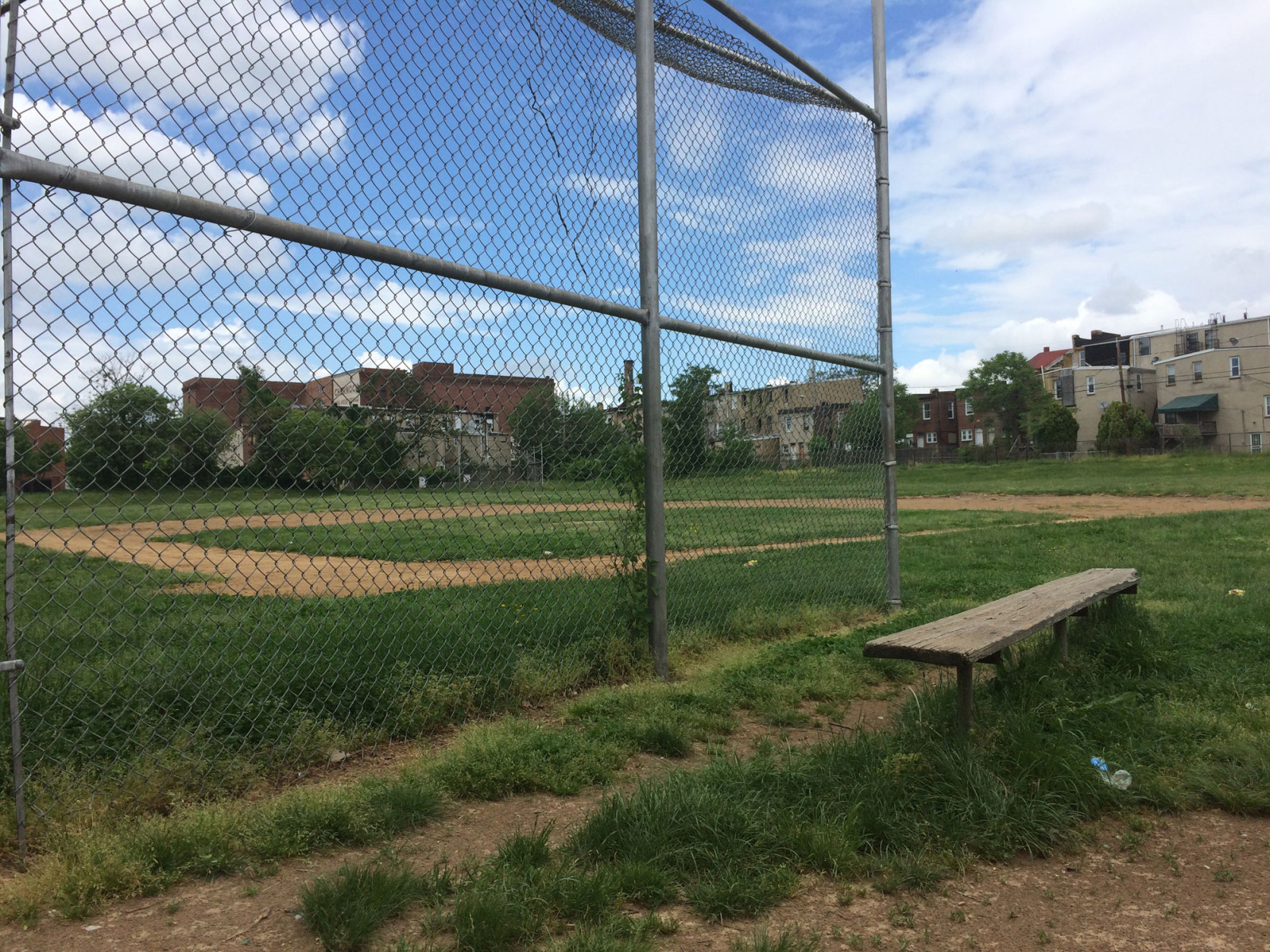 A pair of baseball fields at a youth center in the Upton neighborhood are overgrown and unkempt, as tee ball season doesn't begin until mid-May. (WTOP/Noah Frank)