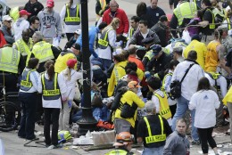 FILE - In this Monday, April 15, 2013 file photo, medical workers aid injured people at the finish line of the 2013 Boston Marathon following an explosion in Boston. (AP Photo/Charles Krupa)