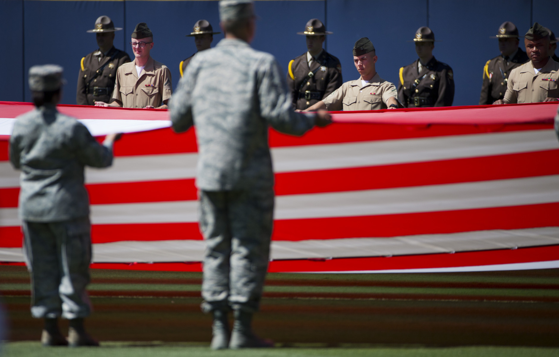 Members of the U.S. military stand at attention while unveiling a giant American flag in the outfield at a Memorial Day ceremony before the start of a baseball game between the Atlanta Braves and the Milwaukee Brewers Saturday, May 23, 2015, in Atlanta. (AP Photo/David Goldman)