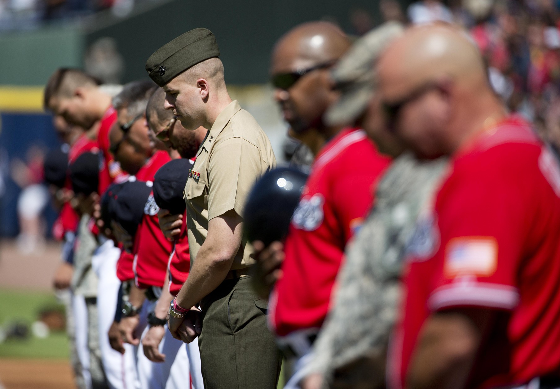 Members of the U.S. military and Atlanta Braves observe a moment of silence at a Memorial Day ceremony before the start of a baseball game between the Braves and the Milwaukee Brewers Saturday, May 23, 2015, in Atlanta. (AP Photo/David Goldman)
