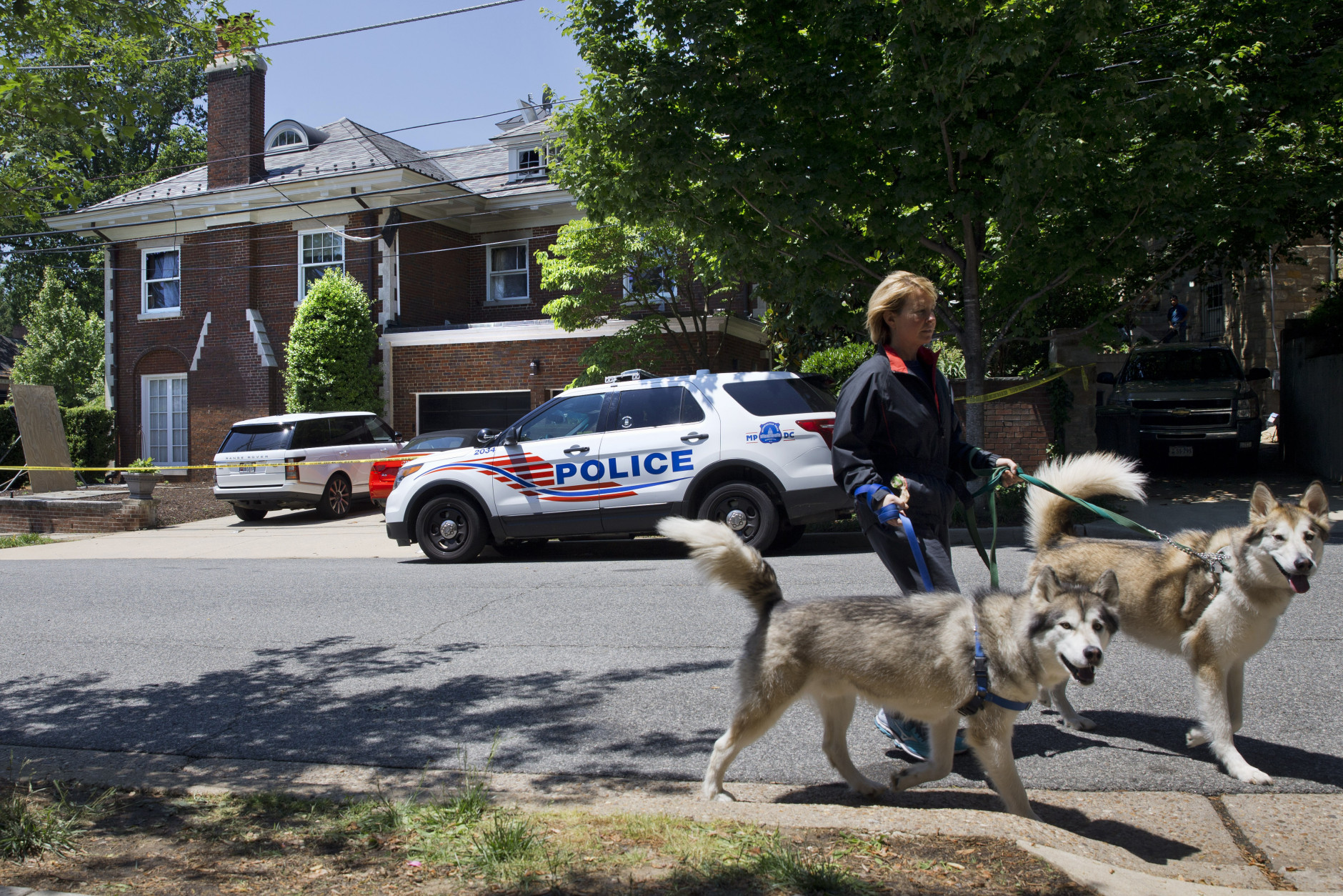 A woman walks her dogs past the fire-damaged multimillion-dollar home in northwest Washington home, Friday May 22, 2015, where 46-year-old Savvas Savopoulos, his 47-year-old wife, Amy Savopoulos, the couple's 10-year-old son Philip, and housekeeper Veralicia Figueroa were found dead May 14. U.S. marshals and police arrested a dangerous ex-convict and took his five companions into custody, safely ending a multistate manhunt in the slayings of a wealthy Washington family and their housekeeper. The fugitive task force tracked Daron Dylon Wint to New York and back before they caught up with him late Thursday (AP Photo/Jacquelyn Martin)