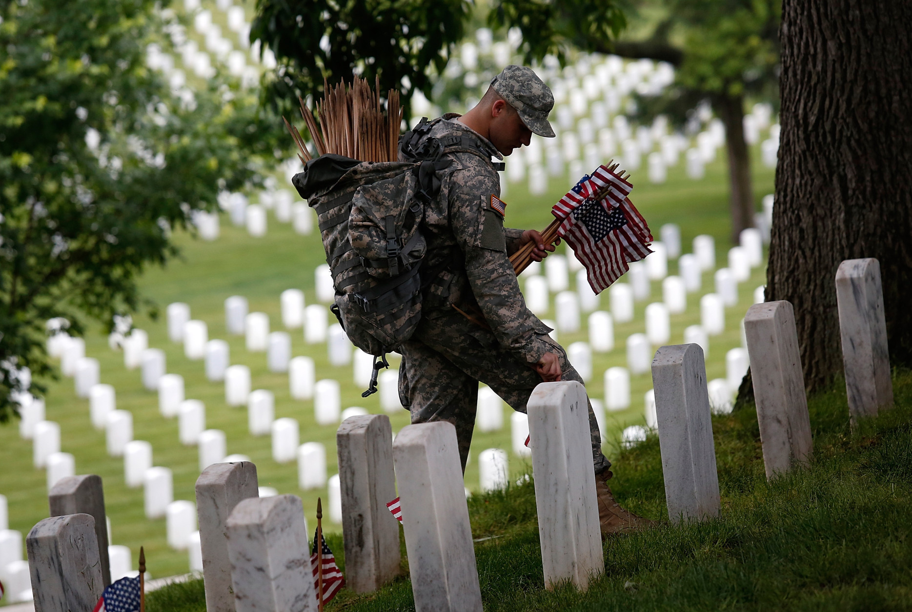 ARLINGTON, VA - MAY 21:  Specialist Michael Escobar of the 3rd U.S. Infantry Regiment places American flags at the graves of U.S. soldiers buried at Arlington National Cemetery, in preparation for Memorial Day May 21, 2015 in Arlington, Virginia. 'Flags-In' has become an annual ceremony since the 3rd U.S. Infantry Regiment (The Old Guard) was designated to be an Army's official ceremonial unit in 1948 (Photo by Win McNamee/Getty Images)