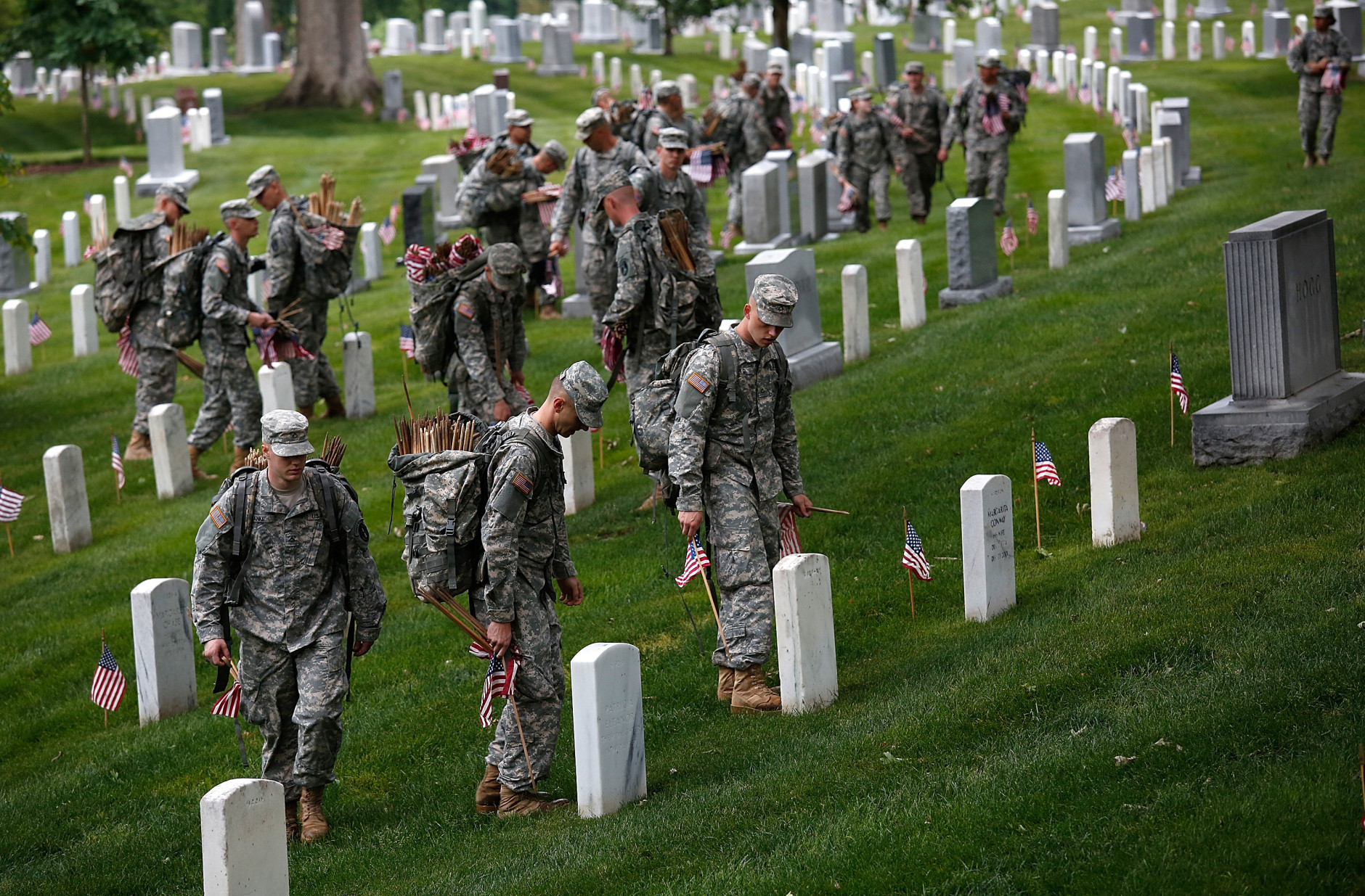 """ARLINGTON, VA - MAY 21: Members of the 3rd U.S. Infantry Regiment place American flags at the graves of U.S. soldiers buried at Arlington National Cemetery, in preparation for Memorial Day May 21, 2015 in Arlington, Virginia. """"Flags-In"""" has become an annual ceremony since the 3rd U.S. Infantry Regiment (The Old Guard) was designated to be an Army's official ceremonial unit in 1948 (Photo by Win McNamee/Getty Images)"""