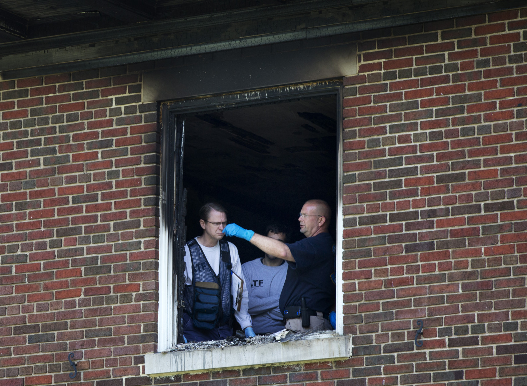 Investigators inspect the fire-damaged multimillion-dollar home in northwest Washington home, Wednesday, May 20, 2015, where four people were found dead May 14. Police Chief Cathy Lanier earlier identified two of the victims found dead as 46-year-old Savvas Savopoulos and his 47-year-old wife, Amy Savopoulos. Police believe the other two victims are the couple's 10-year-old son and a housekeeper. Police say the deaths are being investigated as a homicide.   (AP Photo/Manuel Balce Ceneta)