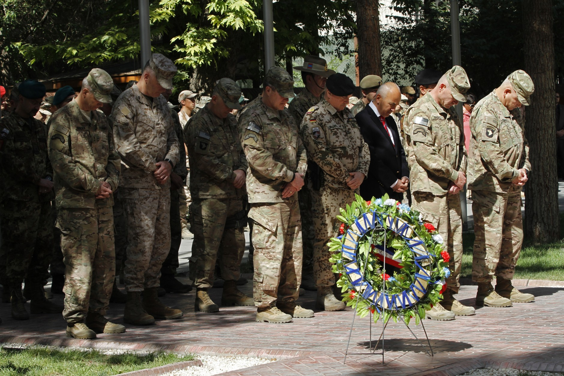 General John F. Campbell, commander of international forces in Afghanistan, second right, gives respect during a ceremony marking Memorial Day at the Resolute Support main headquarters in Kabul, Afghanistan, Monday, May 25, 2015. Over 2,300 American soldiers and more than 11,00 coalition soldiers have lost their lives in action during the last 14 years in Afghanistan. (AP Photo/Allauddin Khan)