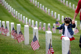 Madelyn Andrews, of Woodland Hills, Calif., walks past military graves while placing flags at headstones in remembrance of Memorial Day, Monday, May 25, 2015, at The Los Angeles National Cemetery in Los Angeles. (AP Photo/Richard Vogel)