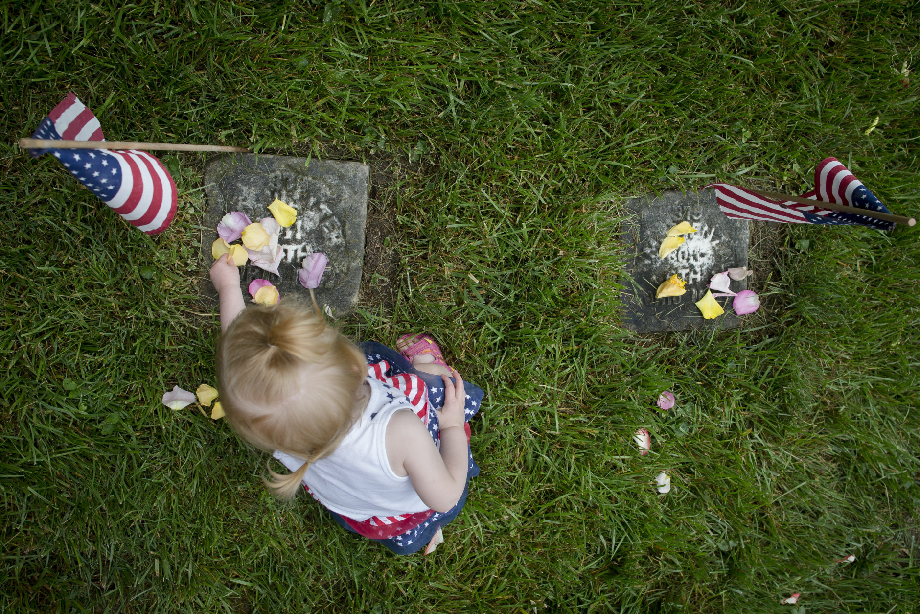 Brielle Nathon, of Lebanon, Ohio, places rose petals on the gravestone of a soldier who died in the Civil War, Monday, May 25, 2015, at Spring Grove Cemetery in Cincinnati. The cemetery is the final resting place of thousands of Civil War soldiers, both Union and Confederate. (AP Photo/John Minchillo)
