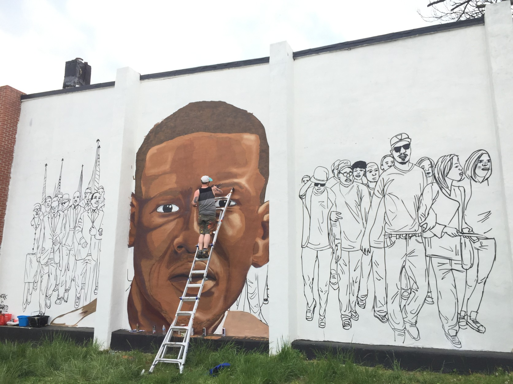 On the other side, the mural depicts modern youth who gathered for Freddie Gray's vigil. (WTOP/Andrew Mollenbeck)
