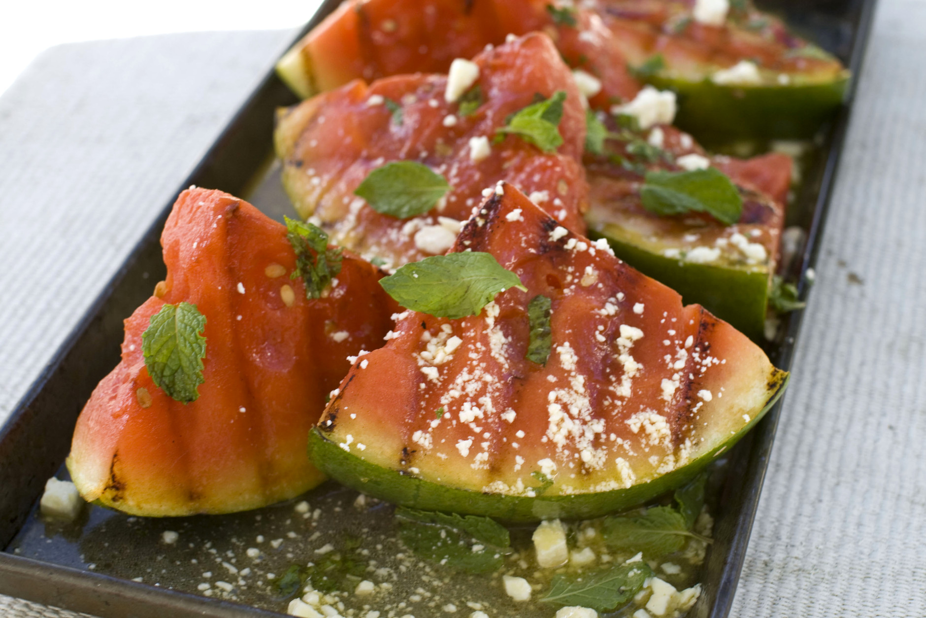 This Aug. 22, 2011 photo shows grilled watermelon salad in Concord, N.H. When ready to serve, place grilled watermelon pieces on a large platter or divide among individual plates.  (AP Photo/Matthew Mead)