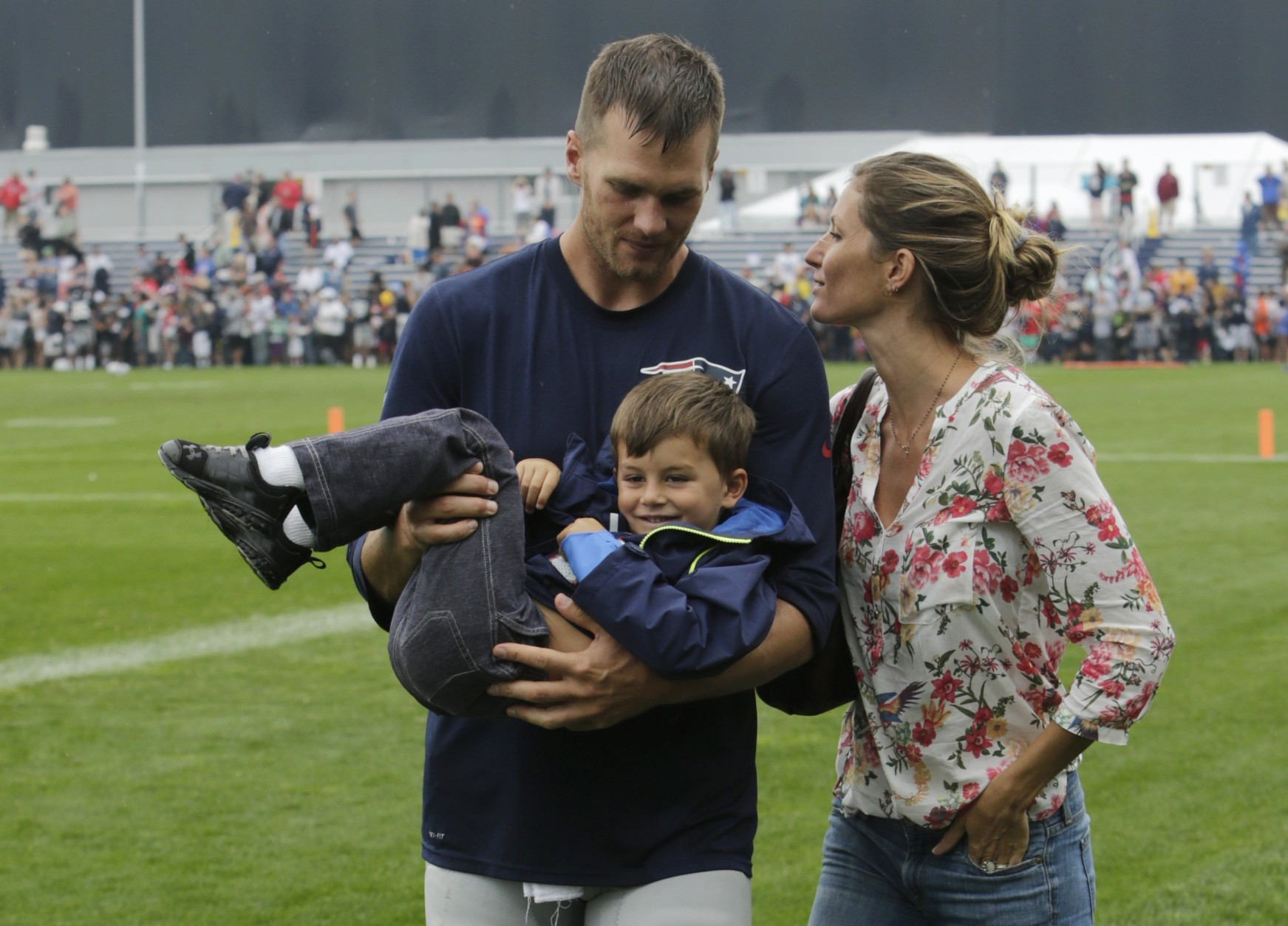 New England Patriots quarterback Tom Brady and his wife Gisele Bundchen with their son Benjamin Brady after a joint workout with the Tampa Bay Buccaneers at NFL football training camp, in Foxborough, Mass., Tuesday, Aug. 13, 2013. (AP Photo/Charles Krupa)