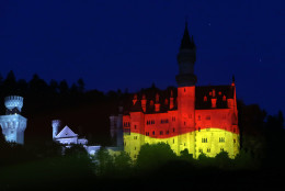 Bavarian castle Neuschwanstein is illuminated with the flag of the Germany ahead of the G-7 summit in Hohenschwangau, Germany,  Friday, June 5, 2015. The summit will take place June 7 and 8 at the Schloss Elmau hotel near Garmisch-Partenkirchen.  (AP Photo/Matthias Schrader)