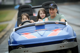 LAKE BUENA VISTA, FL - FEBRUARY 04:  In this handout photo provided by Disney, Emmy Award-winning TV host and Grammy Award-winning comedian Jon Stewart takes a ride on the Tomorrowland Indy Speedway with his children Nate (left, age 6) and Maggie (center, age 5) at the Magic Kingdom theme park on February 4, 2011 in Lake Buena Vista, Florida.  The February 4 visit took place on Maggie's 5th birthday, and Stewart and his family celebrated the occasion with friends at the Walt Disney World theme park.  (Photo by David Roark/Disney via Getty Images)