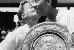 """FILE - In this July 6, 1957 file photo, Althea Gibson of New York city, holding the large gold plate presented to her as the winner of the Women's Singles Tennis title at the All England Lawn Tennis Championships in Wimbledon, London, is kissed by her opponent, Darlene Hard. Gibson became the first black player, male or female, to win Wimbledon when she defeated fellow American Hard in the final. She ended up with five Grand Slam singles titles, including two Wimbledon crowns, and was twice named The Associated Press' """"Female Athlete of the Year."""" Her pioneering didn't end with tennis. In 1964, Gibson became the first black woman to play in the Ladies Professional Golf Association. (AP Photo, File)"""
