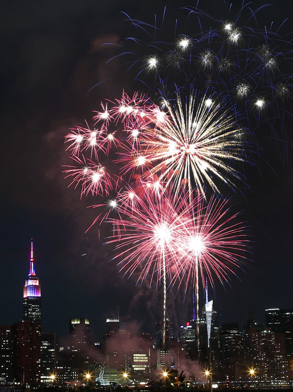 The Empire State Building, left, is illuminated as fireworks explode over the East River in front of the Manhattan skyline, photographed from the Brooklyn borough of New York during the Macy's Fourth of July fireworks show Saturday, July 4, 2015. (AP Photo/Jason DeCrow)