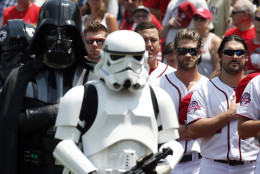 Washington Nationals' Bryce Harper, second from right, and Tanner Roark, right, stand with Darth Vader, left, and a Stormtrooper in costume during the national anthem on Star Wars Day before a baseball game against the Los Angeles Dodgers at Nationals Park, Sunday, July 19, 2015, in Washington. (AP Photo/Alex Brandon)