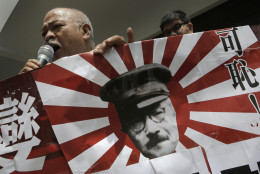"An anti-Japan protester speaks as he holds a Japanese military flag with a cutout picture of Imperial Japanese Army Gen. Hideki Tojo, an executed Class-A war criminal, during a rally near the Japanese Consulate General in Hong Kong, Friday, Sept. 18, 2015, to protest against Japan's ruling Liberal Democratic Party that pushed contentious security bills through a legislative committee. The Chinese words on the flag read: "" Shame ! "" (AP Photo/Vincent Yu)"
