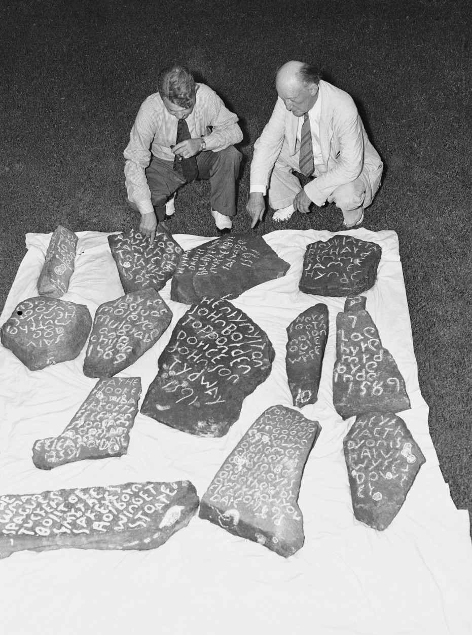"On this date in 1587, an English colony fated to vanish under mysterious circumstances was established on Roanoke Island off North Carolina. In this image, Dr. H.J. Pearce Jr., left, and his father, Dr. H.J. Pearce, are seen as they displayed 13 stones found near Greenville, S.C., which they believed would bring about a solution to the mystery surrounding the fate of Sir Walter Raleigh's ""Lost Colony."" (AP Photo)"