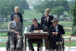 FILE - In this July 26, 1990 file photo, President George H. W. Bush signs the Americans with Disabilities Act during a ceremony on the South Lawn of the White House. Joining the president are, from left, Evan Kemp, chairman of the Equal Opportunity Employment Commission; Rev. Harold Wilke; Sandra Parrino, chairman of the National Council on Disability, and Justin Dart, chairman of The President's Council on Disabilities. TheAmericans with Disabilities Act, which was signed into law 25 years ago, on July 26, 1990.  (AP Photo/Barry Thumma)