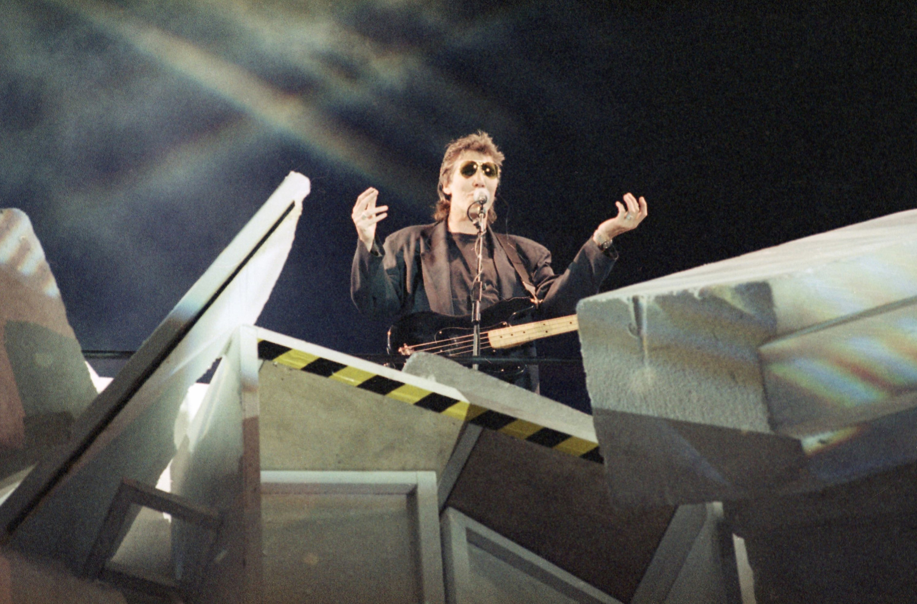 "British musician Roger Waters sits between the stones of the broken wall. The picture was taken during the rehearsal on Friday, July 21, 1990 in East Berlin, and is part of the Roger Waters concert ""The Wall"" which will be performed on Saturday on the former death - strip of the Berlin Wall. ""The Wall"" is an album by the British rock group Pink Floyd that Waters wrote.  He is no longer a member of the band. (AP Photo/Hansjoerg Krauss)"