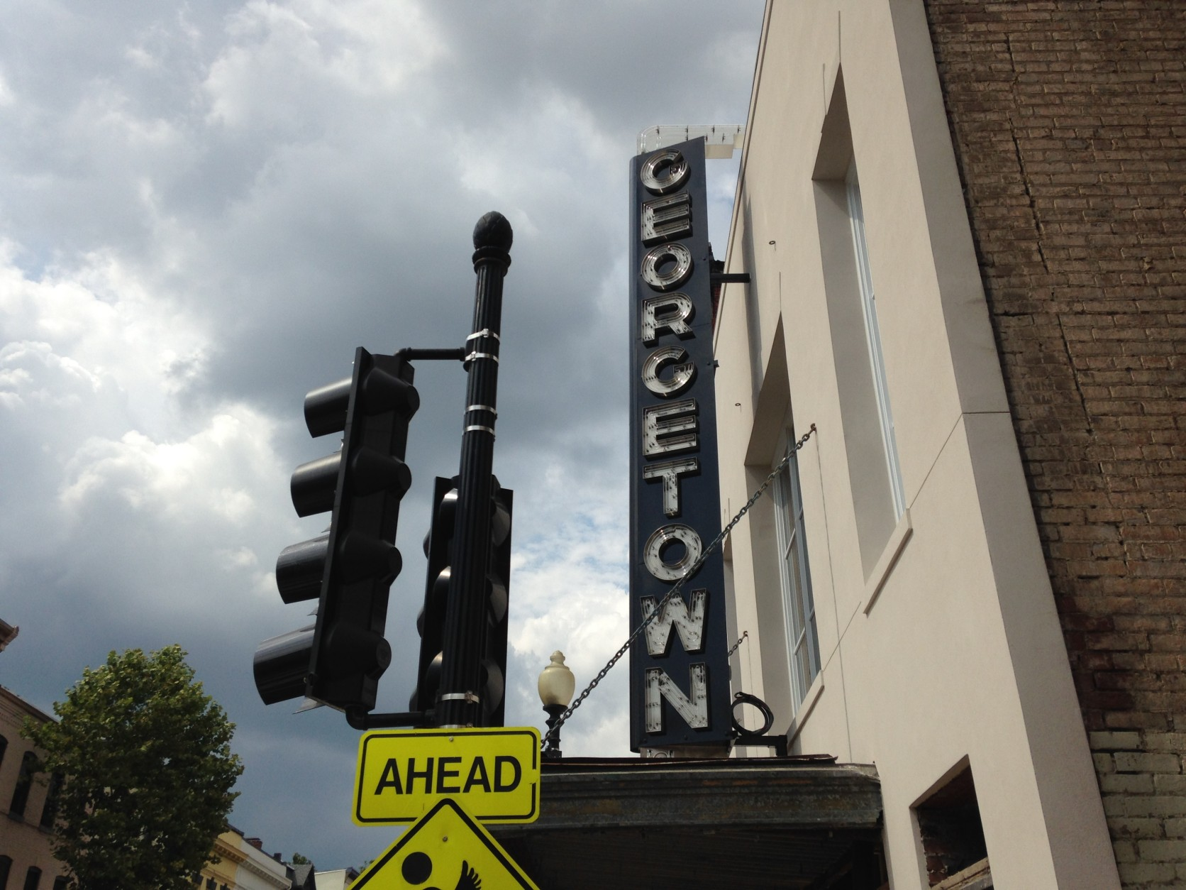 The Georgetown Theater's neon sign, which had been taken down for restoration, was reinstalled Wednesday in its familiar place above Wisconsin Avenue. (WTOP/Michelle Basch)
