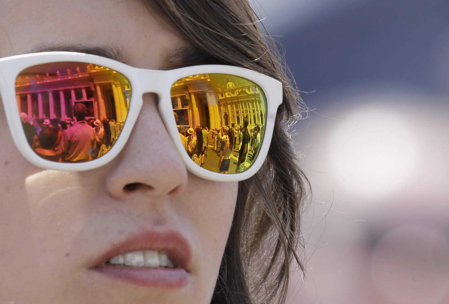 """The St. Peter's Square is reflected on the sunglasses of a woman during the Angelus noon prayer delivered by Pope Francis from his studio's window at the Vatican, Sunday, July 19, 2015. Speaking from his studio window, Francis told the crowd Sunday in St. Peter's Square: """"I see you are courageous with this heat in the square. A tip of the hat to you!"""" Many faithful used sun umbrellas. Temperatures in Rome this week could hit 38-39C (100-102F). Sizzling heat and oppressive humidity have gripped Italy this month, with some nights in Rome seeing """"low"""" temperatures hovering near 30C (86F). (AP Photo/Gregorio Borgia)"""