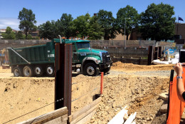 A dump truck carries the final load of dirt out of the excavated hole at The Wharf, a 24-acre redevelopment project along the Southwest Waterfront, on Thursday, July 16, 2015. (WTOP/Ari Ashe)
