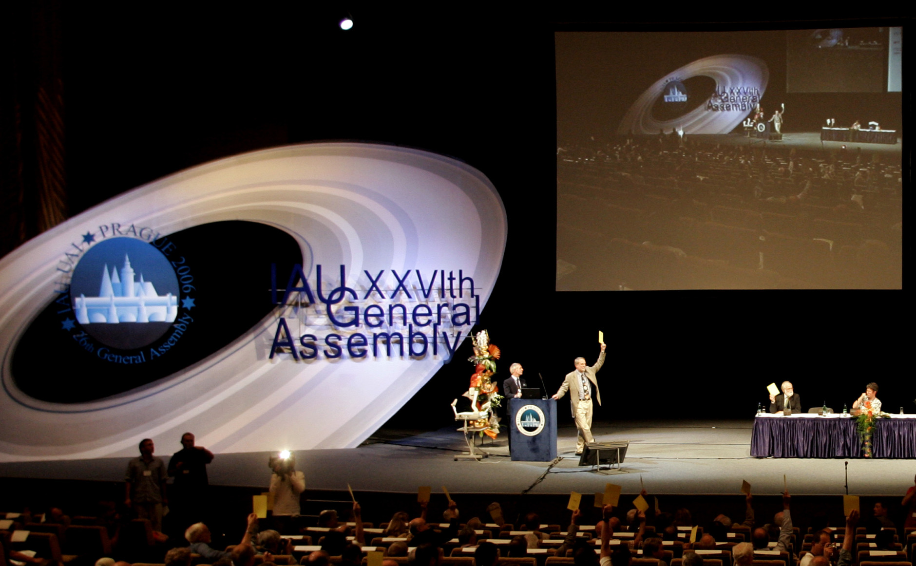 """On this date in 2006, the International Astronomical Union declared that Pluto was no longer a planet, demoting it to the status of a """"dwarf planet."""" Here, members of the IAU are seen voting on the issue. (AP Photo/Petr David Josek)"""