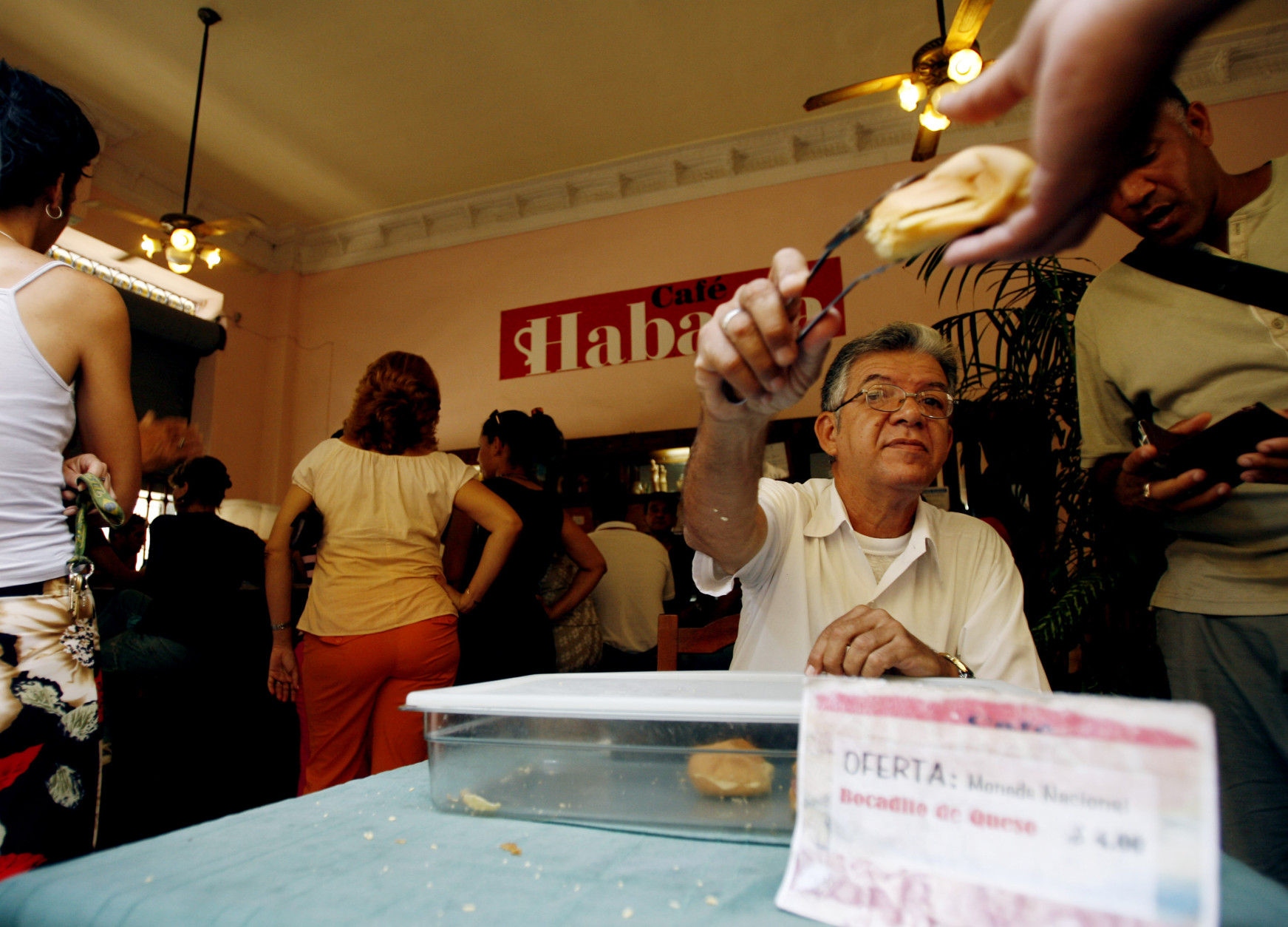 A man sells snacks as Cuban workers take a coffee break at a snack bar in in Old Havana, Monday, June 11, 2007. One of the largest concentrations of venders selling street food for Cuban pesos can be found on Havana's bustling Obispo Street. (AP Photo/Javier Galeano)