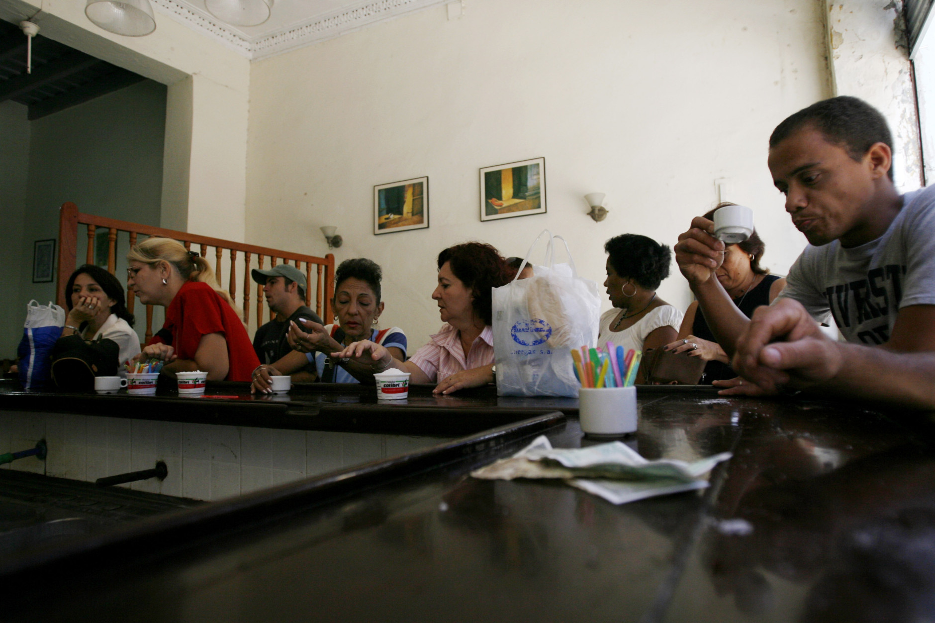 Cuban workers take a coffee break at a snack bar on Obispo street in Old Havana, Monday, June 11, 2007. One of the largest concentrations of venders selling street food for Cuban pesos can be found on Havana's bustling Obispo Street. (AP Photo/Javier Galeano)