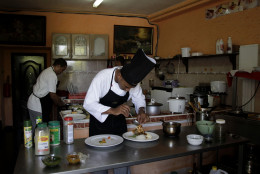 """In this photo taken Friday, April 29, 2011, chef Josue Ferrer prepares a dish at La Moneda Cubana, a private restaurant, in Old Havana, Cuba. A restaurant boom is sweeping Havana under new rules that make it easier to run """"paladars,"""" with a wave of new private eateries opening since January 2011. (AP Photo/Franklin Reyes)"""