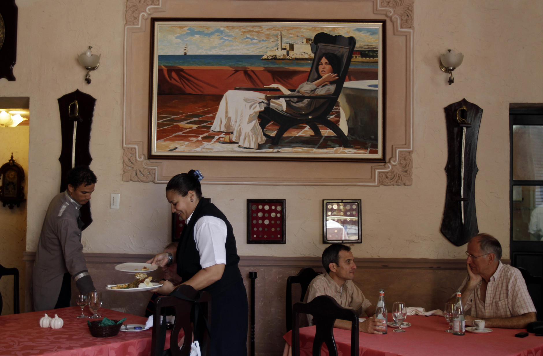 """In this photo taken Friday, April 29, 2011, wait staff attend to customers at """"La Moneda Cubana,"""" a private restaurant in Old Havana, Cuba. A restaurant boom is sweeping Havana under new rules that make it easier to run """"paladars,"""" with a wave of new private eateries opening since January 2011. (AP Photo/Franklin Reyes)"""