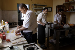 """In this Tuesday, Nov. 29, 2011 photo, workers prepare food at the privately-run restaurant """"El Parthenon,"""" owned by Javier Acosta who operates it from his home in Havana, Cuba. """"This has been a hard year, a year of sacrifice,"""" Acosta said. """"There are days when nobody comes, or when I have just one or two tables, and then there are days when the place is filled."""" Acosta said his costs run to about $1,000 a month, and when business is slow he struggles to break even. Yet the reforms, he says, have changed the face of Cuba, and cynical countrymen who doubt the opening will be lasting must wake up to a new reality. (AP Photo/Javier Galeano)"""