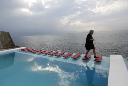 An American tourist walks across the steps of a pool with a view of Havana Bay at Paladar Vistamar in the upscale Miramar section of Havana, Cuba, Thursday, April 19, 2012.  Palardares are privately-run restaurants, usually in private homes, where tourists can dine on higher quality food than the fare generally available in government-run restaurants.(AP Photo/Kathy Willens)