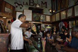 "A bartender pours a drink at the famous restaurant-bar ""La Bodeguita del Medio"" in Old Havana, Cuba, Thursday, April 26, 2012. The restaurant celebrates its 70th anniversary on Thursday. (AP Photo/Franklin Reyes)"
