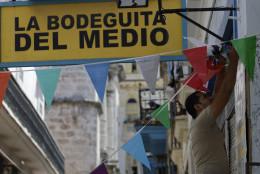 "A worker hangs decorative flags outside the famous restaurant-bar ""La Bodeguita del Medio"" in Old Havana, Cuba, Thursday, April 26, 2012. The restaurant celebrates its 70th anniversary on Thursday. (AP Photo/Franklin Reyes)"