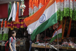 A shopkeeper displays Indian flags at the entrance of his shop in Jammu, India, Saturday, Aug.13, 2016. Shops across the country are laden with flags and other festive paraphernalia as India prepares to celebrate its Independence Day on Aug. 15. (AP Photo/Channi Anand)