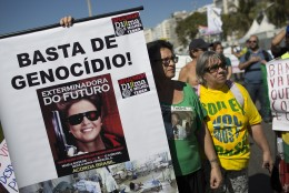 "A woman holds a sign that reads in Portuguese ""Enough genocide!"" and ""Exterminator of the Future"" with an image depicting Brazil's President Dilma Rousseff holding a gun, during a protest demanding the her impeachment in Rio de Janeiro, Brazil, Sunday, Aug. 16, 2015. Demonstrators are taking to the streets across Brazil for a day of nationwide anti-government protests. President Rousseff's second term in office has been shaken by a snowballing corruption scandal involving politicians from her Workers' Party, as well as a spluttering economy, spiraling currency and rising inflation, making her popularity ratings fall to historic lows. (AP Photo/Leo Correa)"