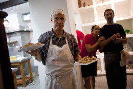 """In this Dec. 7, 2012 photo, U.S. chef Steve Sullivan holds plates of bread as fellow chef Charlie Hallowell, right, looks toward the dining room of the privately-run restaurant Le Chansonnier in Havana, Cuba. Sullivan and Hallowell visited Cuba as part of the """"Planting Seeds"""" delegation that held give-and-take seminars with chefs and culinary students about slow food. They also put on two dinners including a rabbit-based meal at the privately run Le Chansonnier. (AP Photo/Ramon Espinosa)"""