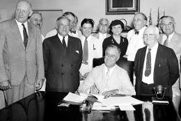 President Franklin Roosevelt signs the Social Security Bill in Washington on August 14, 1935.  The bill will provide old age pensions and unemployment insurance.  From left are: Chairman Doughton of the House Ways and Means Committree; Sen. Wagner, D-N.Y, co-author of the bill, Secretary Perkins, Chairman Harrison of the Senate Finance Committe, Rep. Lewis, D-Md., co-author of the measure. (AP Photo)