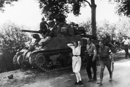 A French woman, accused of being a German sympathizer, is marched along a road past an American heavy tank followed by two armed French partisans on August 19, 1944. She is being taken to Pre en Pail, France, there to be shorn of her hair. (AP Photo)