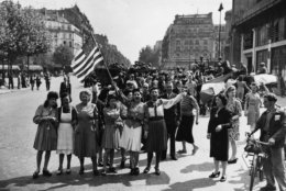 """French civilians with their hastily made American and French flags sing the """"Star Spangled Banner"""" as they greet U.S. and Free French troops entering Paris, France, Aug. 25, 1944, after Allied liberation of the French capital from Nazi occupation in World War II.  (AP Photo/Harry Harris)"""