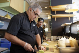 Chef Lucio Alfonso Perez, of Cuba, left, slices avocado for a sushi roll as he works with Kenneth Oliveros, right, at a Sushi Maki restaurant, Wednesday, Aug. 12, 2015, in Miami. Perez is one of four Cuban chefs visiting Miami for the week as part of the chef exchange program being hosted by the Cuba Study Group. The initiative is meant to encourage collaboration and development of new skills. Perez is the chef at Gringo Viejo, which serves traditional Cuban cuisine, and Cuban fusion, in Havana. (AP Photo/Lynne Sladky)