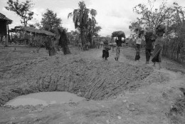 On this date in 1973, U.S. bombing of Cambodia came to a halt. Here, Cambodian villagers walk around bomb crater in road near embattled Takeo 42 miles southwest of Phnom Penh in Cambodia  May 17, 1973.  (AP Photo/Chhor Yuthy)