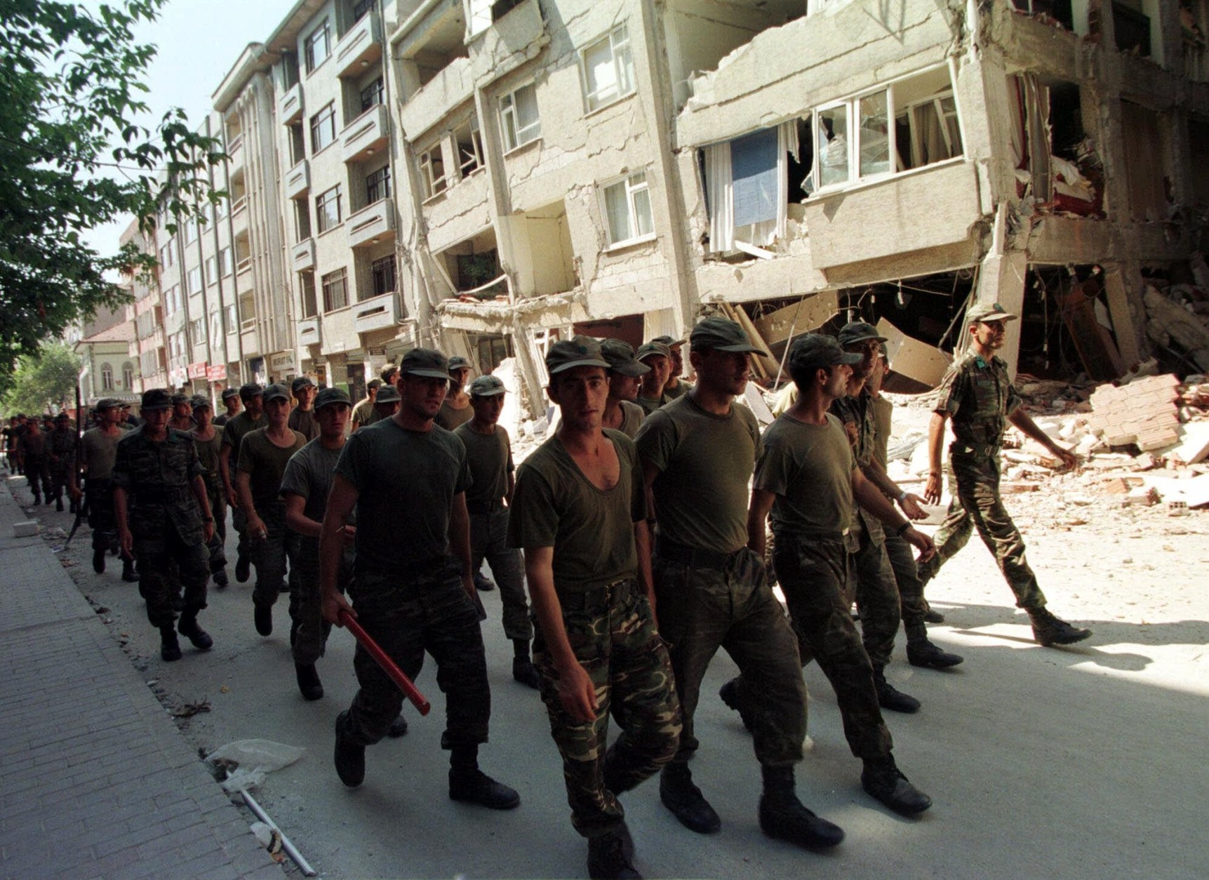 Turkish soldiers participating in rescue operations, walk past devastated  buildings in downtown Sakarya, western Turkey, Wednesday Aug. 18, 1999 after Tuesday's 7.4 magnitude quake. With thousands of people reported missing along an 80-mile arc of destruction left by a devastating earthquake, disaster relief teams from around the world Wednesday joined overwhelmed Turkish rescue crews in the hunt for bodies and survivors. (AP Photo/Burhan Ozbilici)