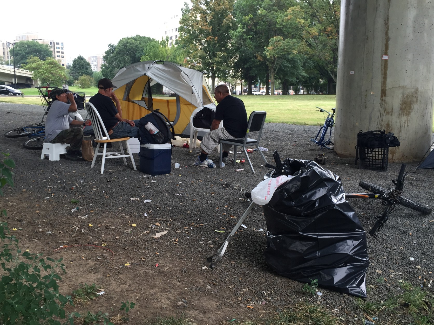 Dozens of homeless camps are scattered throughout Washington, D.C. Here, a group of men sit under a bridge along Rock Creek Parkway in Northwest. (WTOP/Andrew Mollenbeck)
